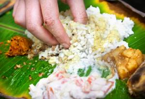 Man eating Indian traditional vegetarian thali from rice, dal, potatoes, tomato salad on banana leaf in restaurant