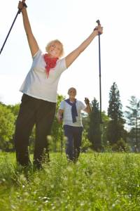 Two active seniors hiking together in nature in summer